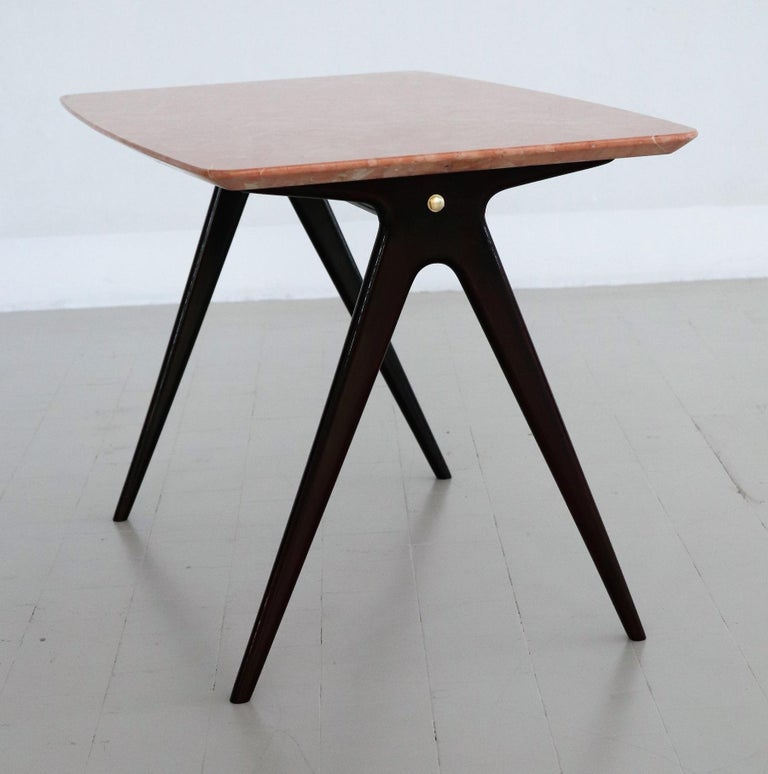 Beautiful particular coffee table with gorgeous pink marble top, brass screws and wooden legs. Made in Italy during the 1950s. Reminds to the style of Gio Ponti. This pink marble has a beautiful natural marble design, rare to find in such a great
