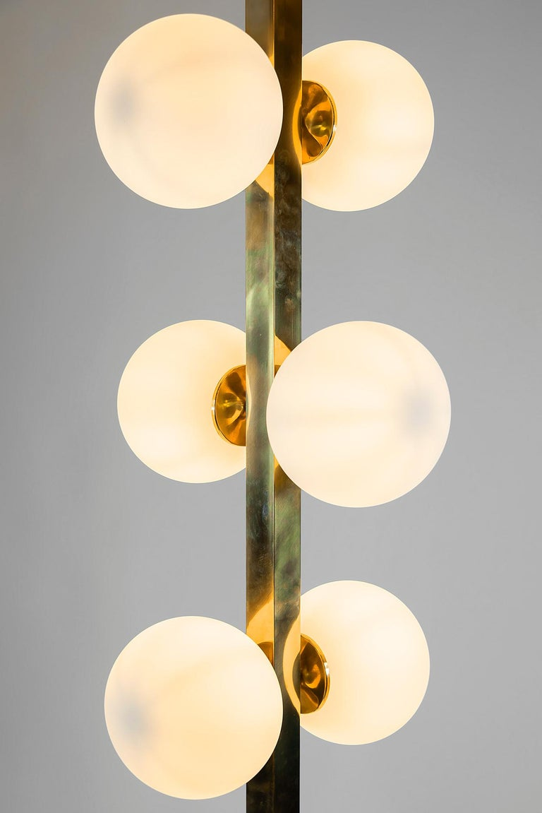 Italian midcentury design floor lamp is made of rectangular satin finish brass stand on 4 branch leg. It goes with 10 lamps including bulbs E27. The glass shades are white color matte finish. Measurements: 37 x 37 x 200 (H) cm, legs 59 x 59 cm,