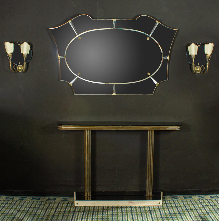 Italian midcentury design brass console table with a fume mirror top and a white marble finished base . the set include the Mirror and a pair of brass mounted Sconces. Elegant solution for an entrance or a dining room. Measurements: Console