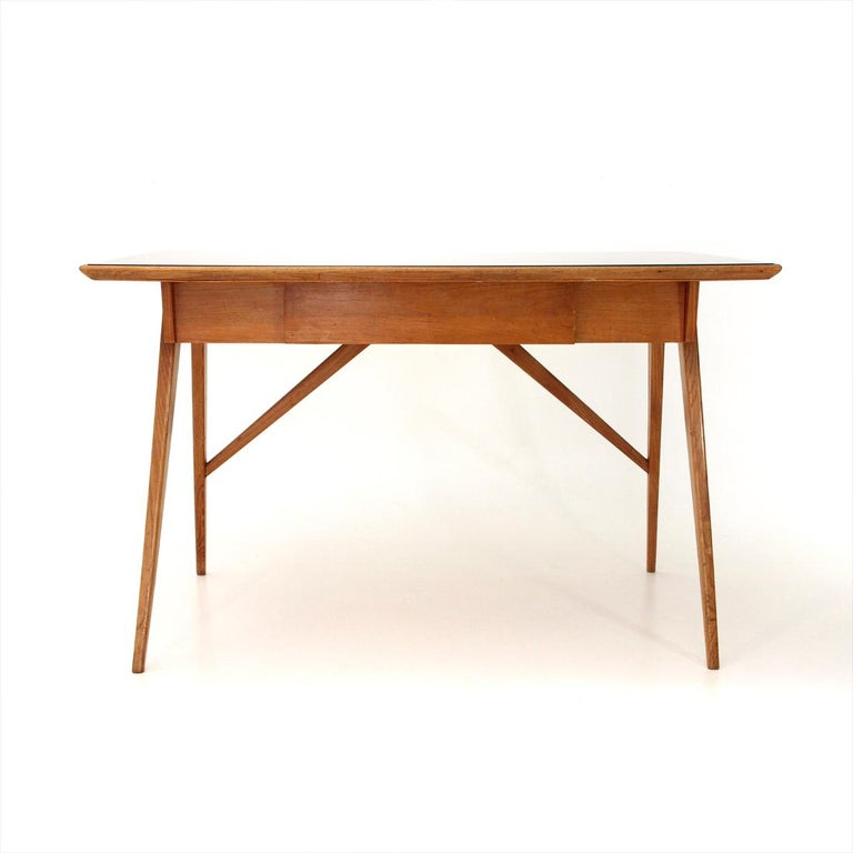 Italian manufacturing desk produced in the 1950s. Rectangular wooden top with framed black glass. Tapered wooden legs. Central drawer. Good general conditions, some signs due to normal use over time, small stroke on the drawer.  Dimensions: