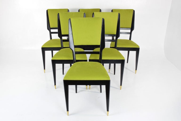 20th century vintage set of six Italian dining chairs composed of ebonized wood designed with a mid-panel backrest. The two front legs have beautiful brass ending creating a striking design effect.   Fully restored through re-finishing and