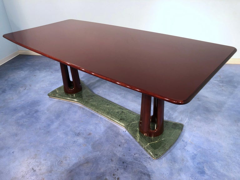 This masterpiece has been manufactured by Vittorio Dassi in 1950 and is a magnificent example of the Italian design of the period. It composed of precious mahogany wood, fine colored glass on the top, and Dolomiti Green Alps marble banded with