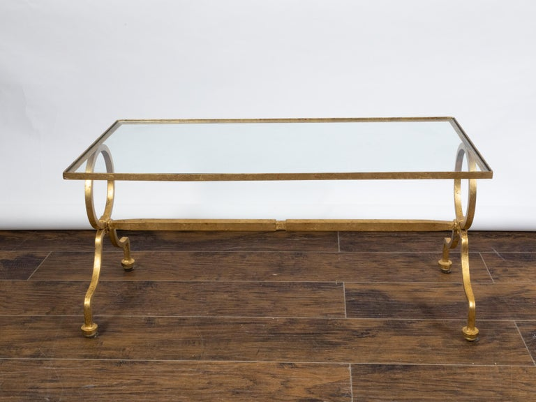 An Italian gilt iron coffee table from the mid 20th century, with glass top, rings and scrolling feet. Created in Italy during the midcentury period, this gilt iron coffee table features a rectangular glass top sitting above two large rings resting