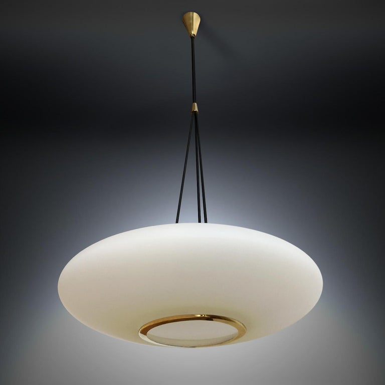 Superb Italian light pendant manufactured by Stilnovo in the 1950s. The oval brushed satin glass diffuser is suspended from enameled metal arms and finished with original brass details. It's in very good conditions of the period, with slight signs