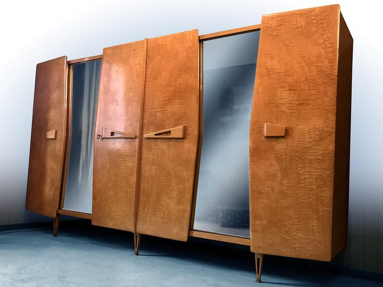 Stylish Italian Armoire with sliding mirror doors designed by Vittorio Dassi in the 1950s and direct expression of Gio Ponti's design with whom he collaborated for a long time. The cabinet is made of a gorgeous yellow maple and supported on wood