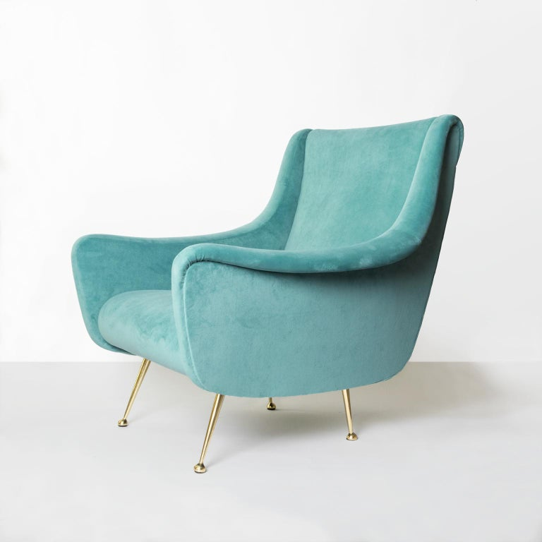 A Midcentury Modern lounge chair newly restored and reupholstered in blue-green velvet. The newly polished legs are solid brass. Made by Lenzi has original metal label.   Measures: Height: 33