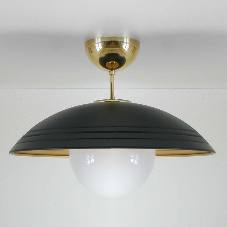 This semi flush mount was made in Italy in the late 1960s, early 1970s. It has got a black lacquered and gilt colored metal lamp shade, white opaline glass globe and brass details.  The light requires one E14 bulb.  Rewired for use in US.