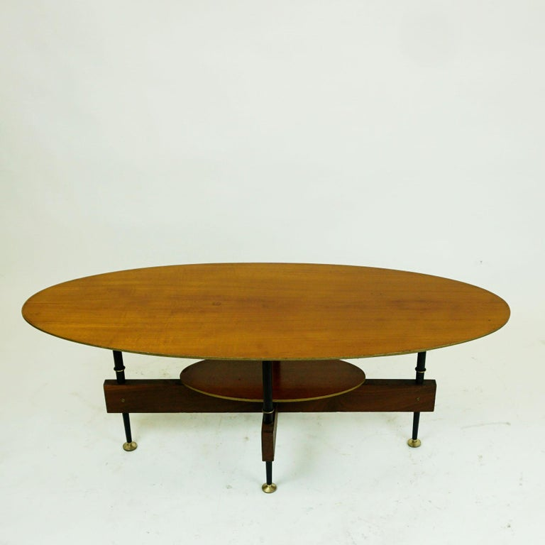 Small elegant Italian midcentury teak cocktail or coffee table designed in the 1950s. It features a oval teak wood top and black lacquered metal legs with brass details.