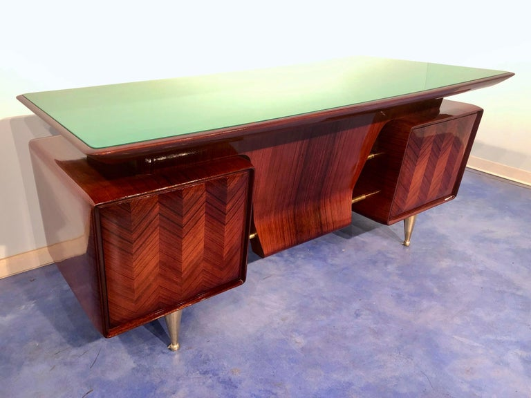 This stunning Italian executive desk is a masterpiece designed and attributed to Vittorio Dassi, a model type produced in Italy circa 1954 and specifically dedicated to an audience formed by professionals and senior managers. Its rosewood structure