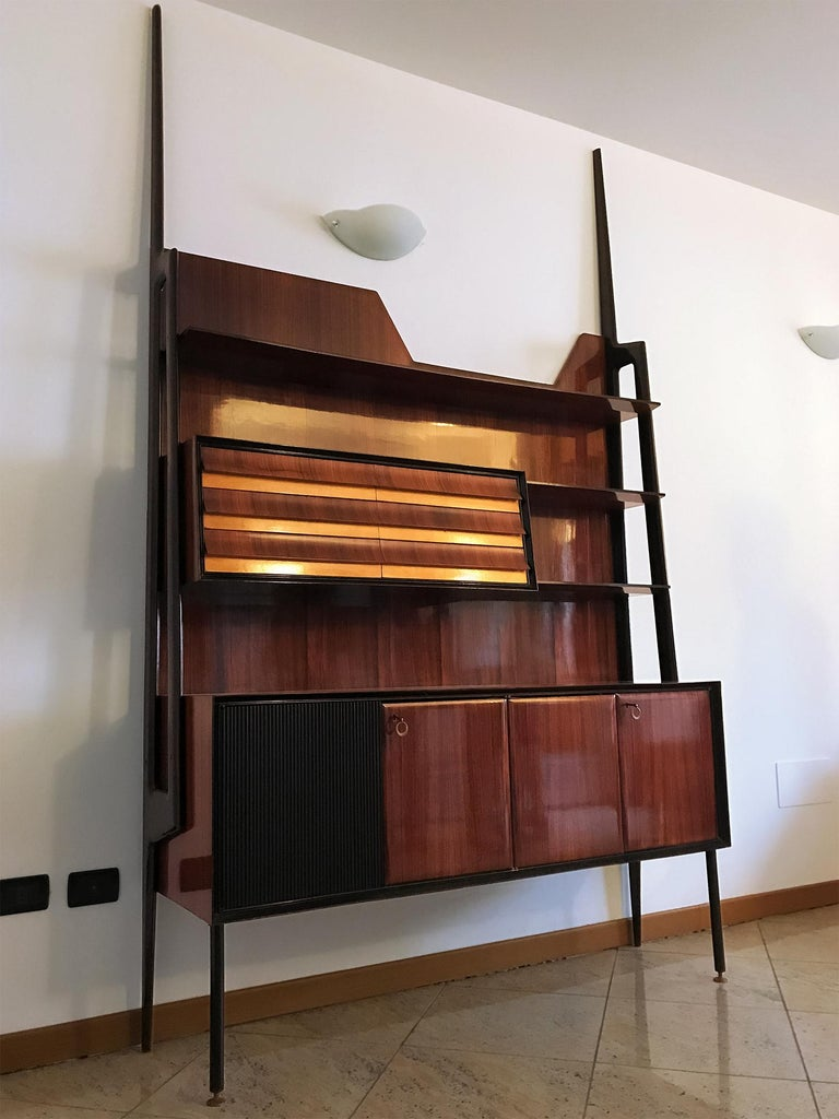Stunning Italian self-standing bookcase designed by Vittorio Dassi in the 1950s. The structure is of veneered rosewood, equipped with drawers, and supported by uprights with the form of long lances in ebony stained wood. The item is in good