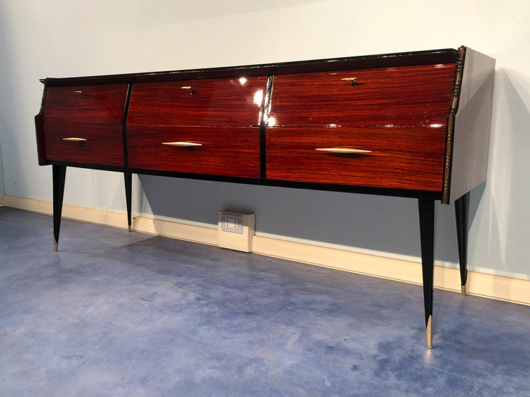 Beautiful Italian midcentury sideboard, or chest of drawers in refined rosewood with elegant details such as the brass handles and the arched line front. The top is in black glass, the interior of the six drawers are in maple, the legs finish in a
