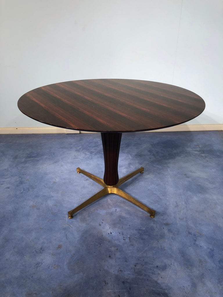 This Italian midcentury rosewood table attributed to Paolo Buffa 1950, is an example of pure Italian design on the period. The round top is completely in rosewood with spectacular color and texture. The central mahogany leg has grooves, typical of
