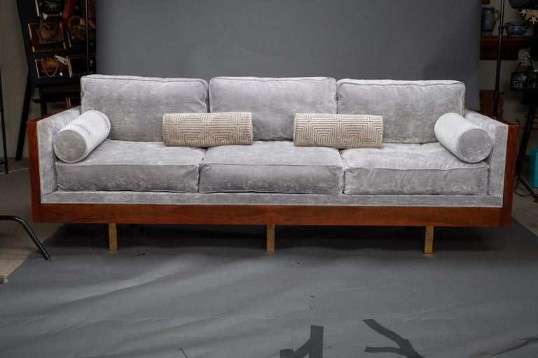 Sofa is re-upholstered in a grey velvety fabric. It has 3 big sit cushions and 3 pillows for the back support. 2 small cylindrical decorative pillows are also included. Frame of the sofa is made out of walnut wood. It is elevated by 4 small legs on