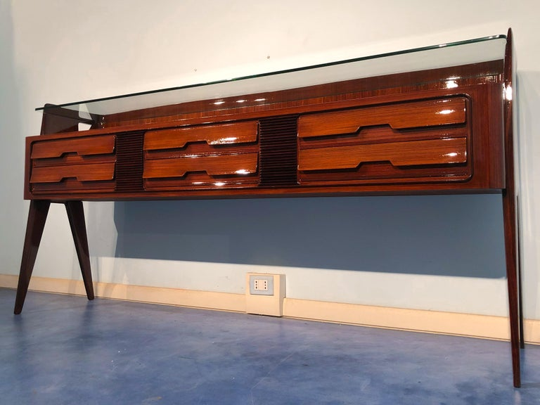 Italian midcentury teak sideboard by Vittorio and Plinio Dassi. The refined design of this piece can be seen in many details, for example, the jutting line of the drawers, the sections with a horizontal line (grissinatura) that divide them, the