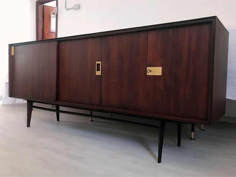 This sideboard has been crafted with a gorgeous material like as teakwood, and it's finished with brass details. It's offers plenty of room for storage, the internal cabinets are equipped with shelves and on the left side a sliding door hide