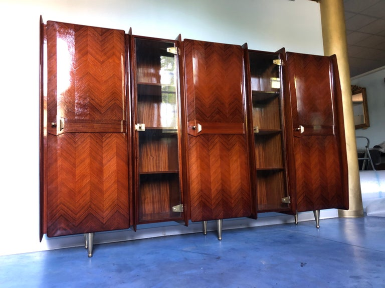 This wonderful Italian sideboard, bookcase, or vitrine has been manufactured by Vittorio Dassi, 1950 and it is a splendid example of the Italian design of the period.  Stunning teakwood doors texture divided by two locking glazed sections with