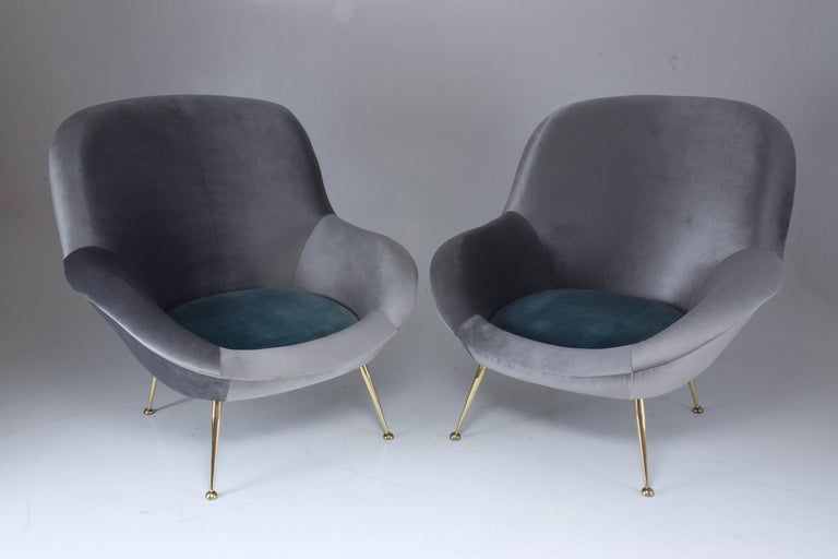 A rare pair of 20th-century Italian armchairs manufactured by ISA Bergamo and designed in an organic curved shape with a cushioned outer ring and comfortable depth which sit on splayed polished brass legs. In fully restored condition and