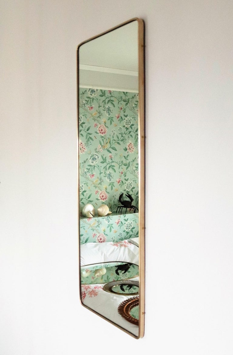 Gorgeous and elegant vintage wall mirror with deep solid brass frame and crystal mirror glass. Made in Italy in the 1950s, original; this is no reproduction. The brass frame have been polished. The mirrored glass have been renewed. At the backside