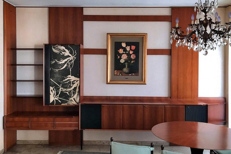 This is a living room well designed by Vittorio Dassi in the 1950s. It's a wall unit, with several compartments, hinged doors, drawers and open shelves which offering plenty of storage space and it would be a great addition to any modern interior