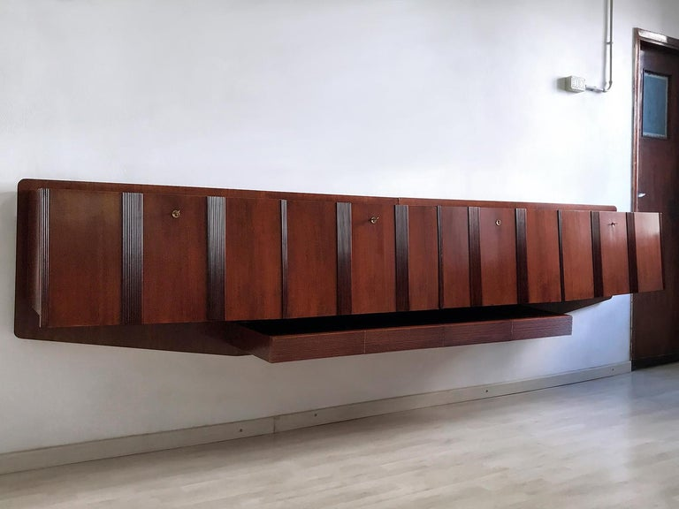 Stunning and very rare Italian wall-mounted Sideboard of the 1950s, a real unique piece well designed in the manner of Paolo Buffa or Vittorio Dassi. Its uniqueness is given by different factors, first one the impressive dimensions of its walnut