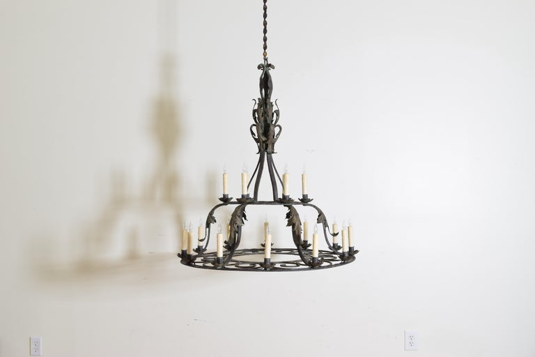 beautifully wrought iron frame with concentric circles and foliate metal mounts, having two tiers the top with 6 lights and the bottom with 12 lights, retaining original faded green paint 1st q 20th century.