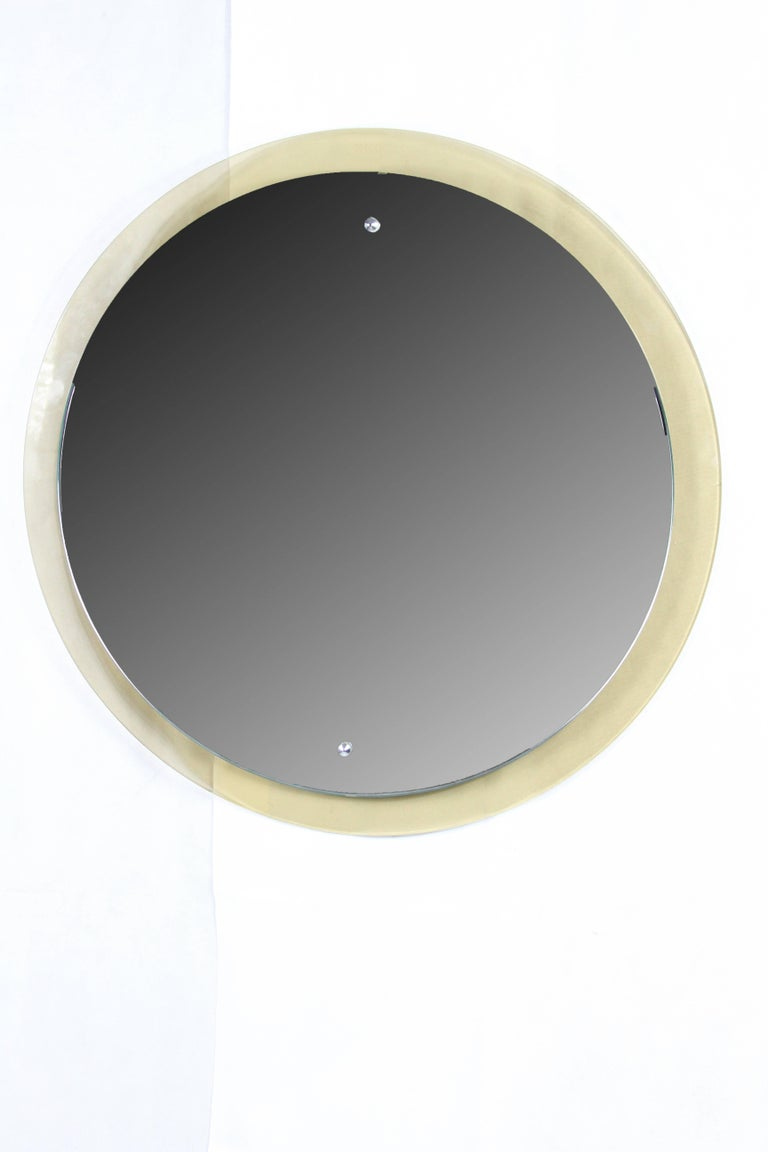 """Mirror from the studio """"Cristal Art"""" (1944-1996 Turin). The mirror border ends conical and is fixed with two rivet on a smoked glass base. On the backside labelled with Cristal Art. Excellent conditions."""