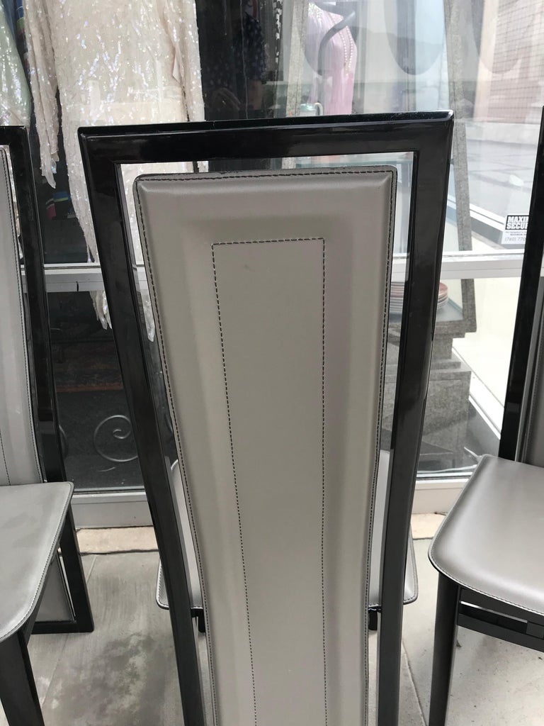 Made by A. Sibau in the early 1980s in Italy, are a set of 6 Italian modern dining chairs. Ebony lacquer wood with dove grey leather seats and backs. The design is very unique as the high backs are