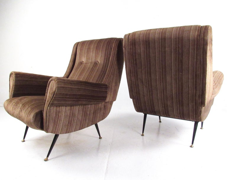 This striking pair of 1950s Italian modern lounge chairs feature sturdy mid-century construction and unique tapered metal legs. The shapely sculptural design in the style of Gigi Radice is complimented by the vintage upholstery. Please confirm item