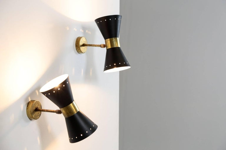 Italian modern diabolo sconces. The lampshades are adjustable and can light in different directions. Two bulbs per lampshade. Excellent condition, beautiful sculptural and decorative wall light style Stilnovo.