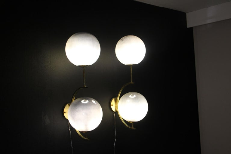 These sconces are very elegant with their brass frame and their large silver Murano glass globes . When light is off ,they are completely silver mirror color and when light is on,they turn to irregular silver reflects.  They have got very unusual