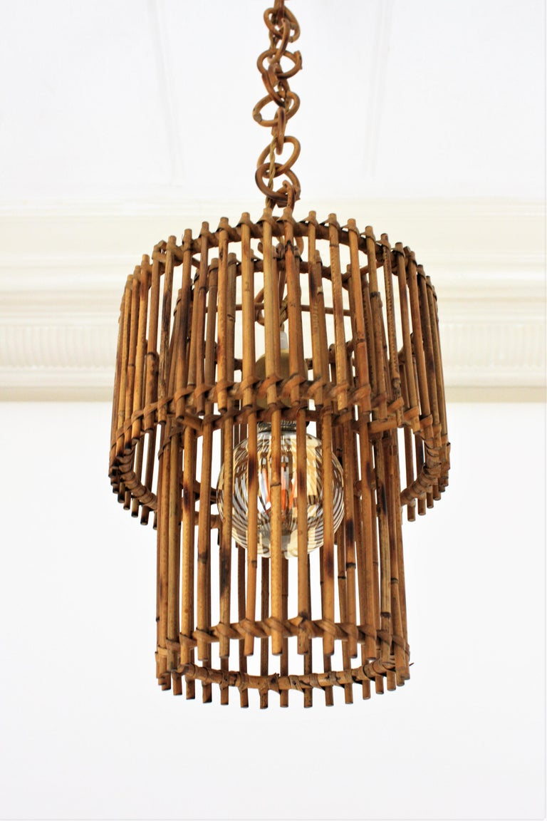 Eye-catching Mid-Century Modern cylinder rattan lantern or pendant ceiling lamp, Italy, 1960s. This oriental inspired suspension features two concentric cylinders made of rattan or wicker canes. The outer cylindrical shade is 25 cm diameter and the