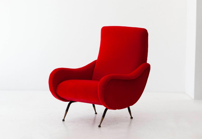 This Italian lounge chair was produced during the 1950s Black enameled iron frame with brass socks Fully restored: new red cotton velvet upholstery and padding The legs have been painted with new black, only the brass has original patina (a