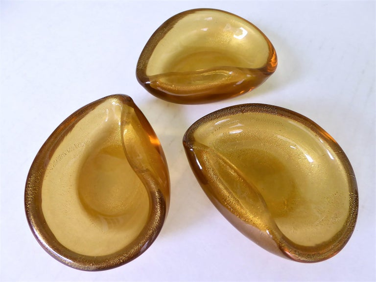 Wonderful Murano creations. Three clam shell or ear shaped vessels of blown glass with gold leaf inclusions. Wonderfully blown and shaped. For use as salt cellars or originally probably as small individual ashtrays.  Measurements each: 3 1/2