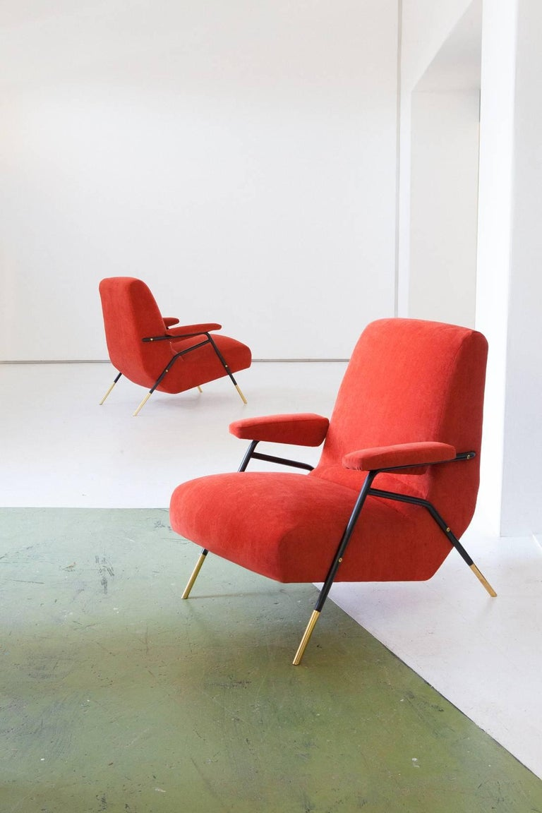 Pair of lounge chairs, Italy, 1950s These easy chairs with armrests has a black enameled Iron and polished brass frame, new orange velvet upholstery (the orange is more closed to the red than the yellow, also the padding is replaced). This