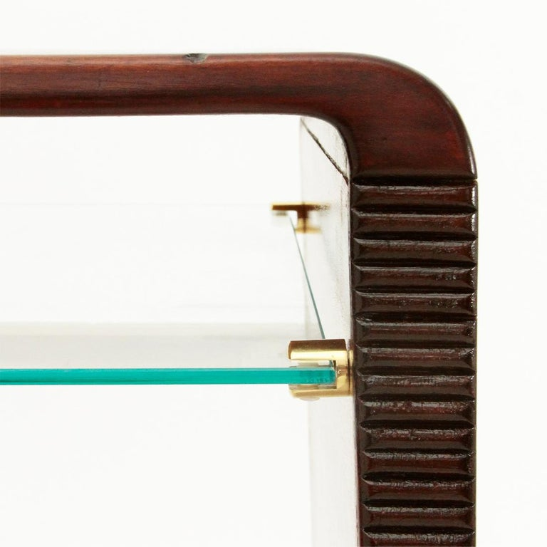 Consolle/Scrivania di manifattura italiana eseguita negli anni '40. Struttura in legno impiallacciato con bordi curvi. Gambe leggermente bombate con rastrematura finale e cornice frontale in legno intagliato. Mensola in vetro trasparente con