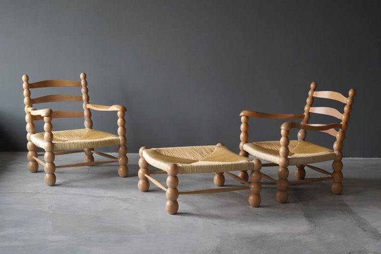 A pair of lounge chairs / armchairs. Executed in finely carved European beech and rattan. Produced in Italy 1960s. Expresses a visual language similar to that of works by Paolo Buffa or Jean Royere.
