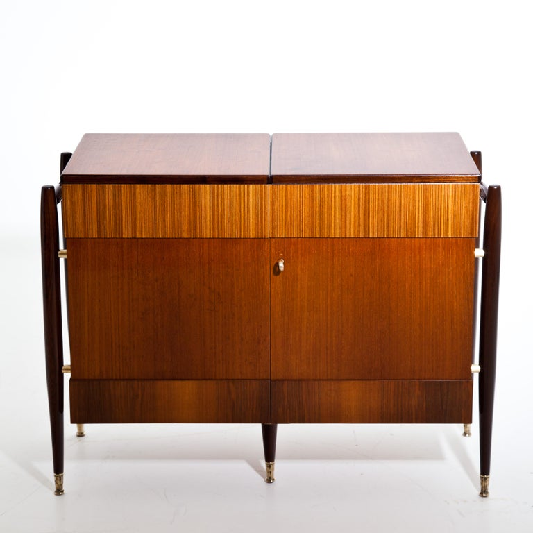 An Italian modernist folding bar cabinet. Bar folds open in the middle and is finished on all sides to be free standing. Mahogany, teak, patinated brass details.