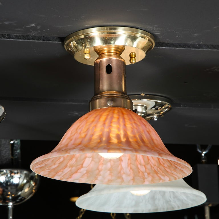 This refined modernist flush mount was realized in Murano, Italy- the island off the coast of Venice renowned for centuries for its superlative glass production- during the 20th century. It features a billowing convex shade in mottled sherbert glass