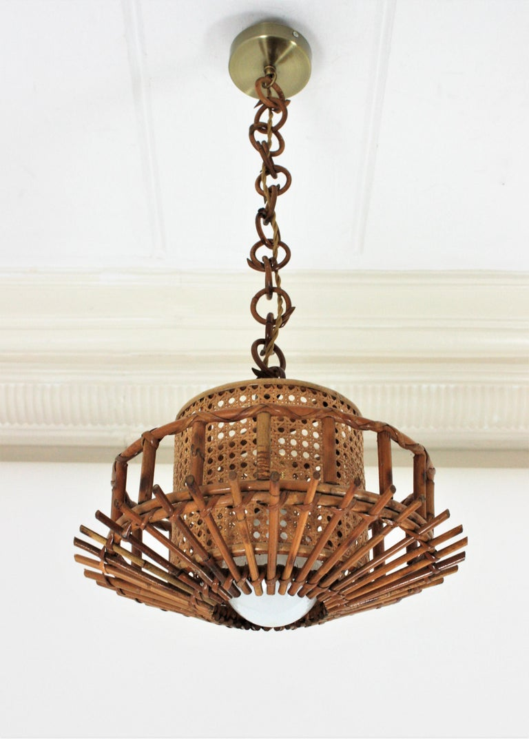 Beautiful Mid-Century Modern woven wicker wire and rattan pendant lamp / lantern, Italy, 1960s. This suspension lamp has an structure made of rattan canes and an inner wicker wire cylindrical shade. It hangs from a chain with round rattan links