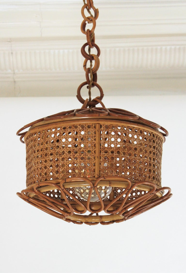 Beautiful Mid-Century Modern woven wicker wire and rattan pendant lamp / lantern, Italy, 1950s. The woven wicker cylindrical shade of this lamp is accented by handcrafted rattan details as petals at the bottom and at the top. It hangs from a chain