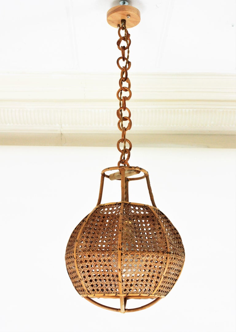 Mid-Century Modern woven wicker wire and rattan globe shaped lantern or pendant ceiling lamp, Italy, 1950s.  The woven wicker spherical shade of this lamp is accented by rattan details. It hangs from a chain with round rattan links that can be cut