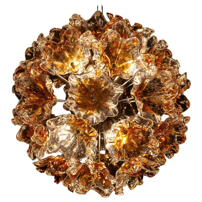 Large midcentury Sputnik chandelier composed of 38 precious hand blown Murano flowers art glasses with amber color inclusion. This amazing fixture fills the room with a warm and welcoming glow. Chromed steel spherical frame, with six E 27  \ 5 W