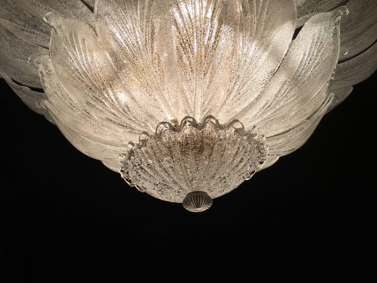 Realized in pure Murano glass consists of an incredible number of leaves. The structure is gilt-metal. 18 lights spread a magical light. Available 3 of this item.  Measures: Diameter 100 cm, height 46 cm without the chain.