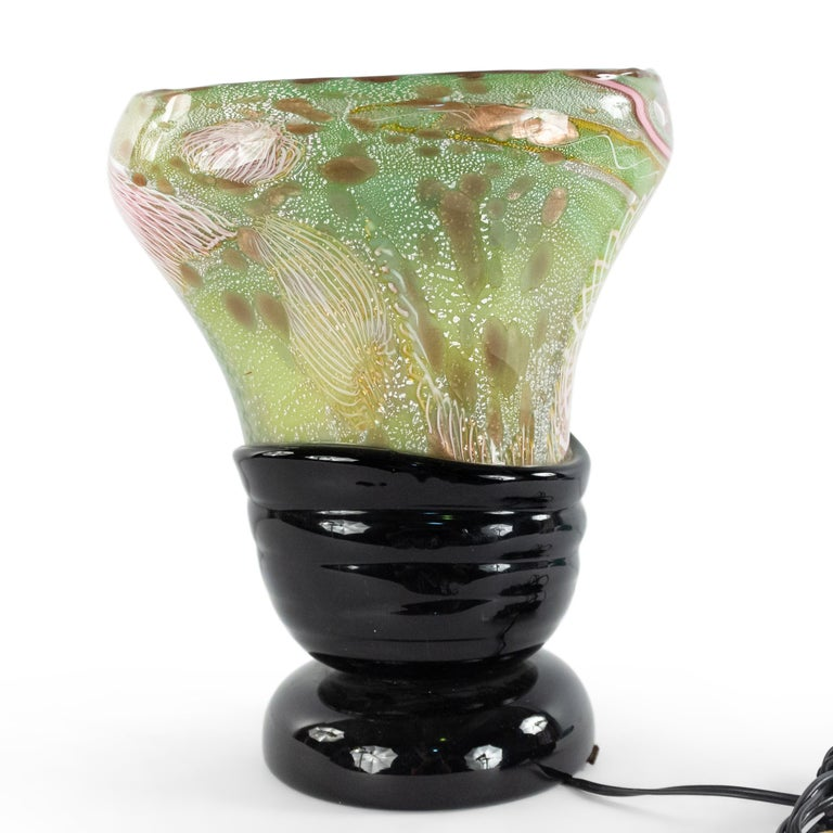 Italian 1960s Venetian Murano glass oval shaped table lamp of vase form with green, pink, and white freeform design on a round applied black glass base. (att: Nichetto).
