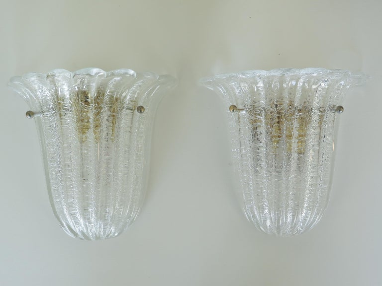 Beautiful pair of Italian Murano glass sconces by Barovier&Toso. Fluted shell shape with scalloped top edge, wavy ribbed glass and brass ball detailing. Brass plated metal backplate with one socket, newly rewired. 5 sconces available, sold as pairs