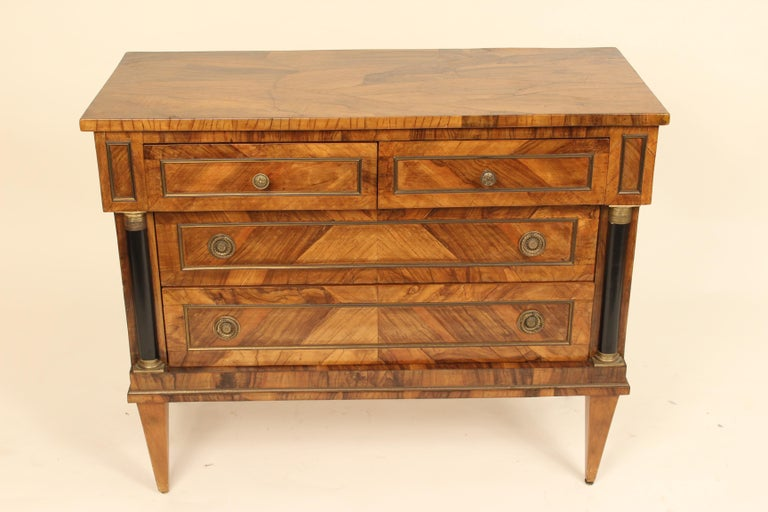 Italian neoclassical style burl olive wood chest of drawers with ebonized columns and brass hardware, mid-20th century.