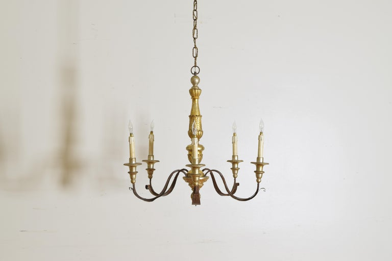 Having a central and segmented carved giltwood standard in the neoclassical taste with acanthus details, issuing 5 iron arms with metal leaf decoration, the arms with silvered wooden bobeches, second quarter of the 19th century.