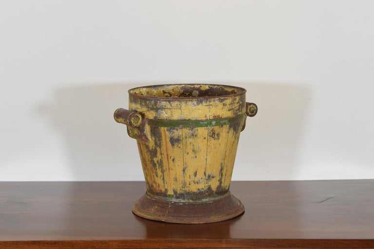 In the neoclassical taste with yellow and green painted tole surfaces, the tapering body surmounted atop a plinth base and having rounded handles, the interior with the original pierced liner, the bottom rusted open in areas.