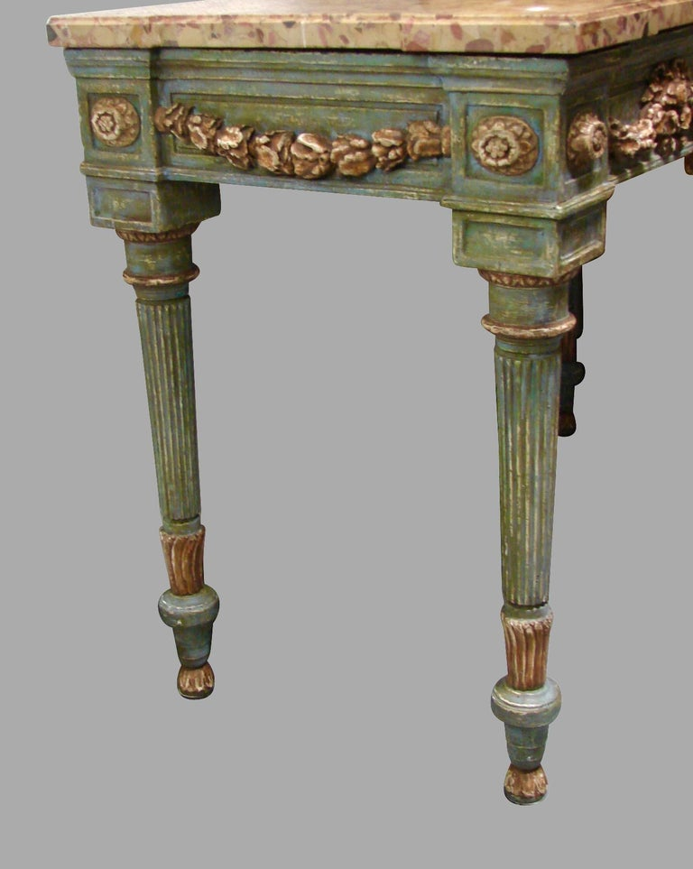 A pretty Italian neoclassical cream and grey painted console table, the Breche d'Alep marble top supported by a highly carved painted base with a central cartouche and floral swags, the sides similarly executed, supported on round tapered reeded