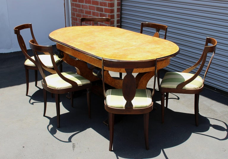Table and six chairs set, burl maple veneer top and walnut base. Chairs reupholstered in original material from the period. Tabletop can be dismantle for easy transport.